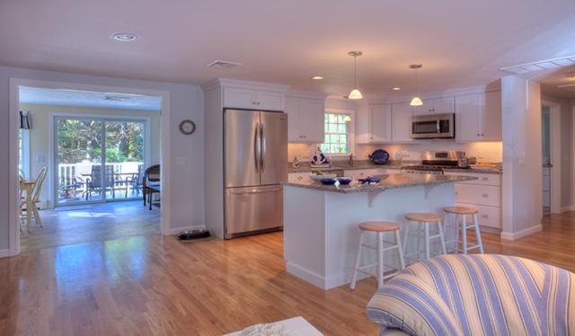 Kitchen, living room and sun room on open floor plan with hardwood floors